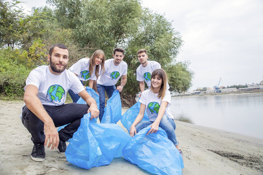 Teenage volunteers doing garbage cleanup on riverbank