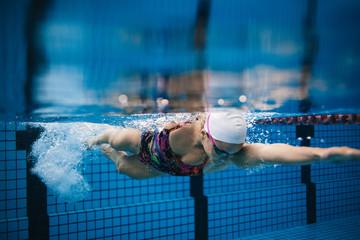 Female swimmer in action inside swimming pool.