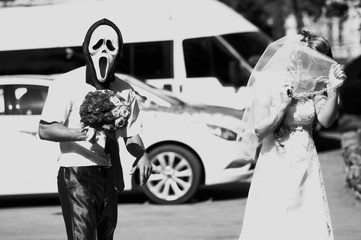 the groom wearing a mask scared the bride at the wedding. black and white photo