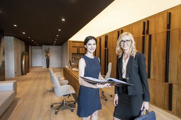 Two businesswomen talking over document