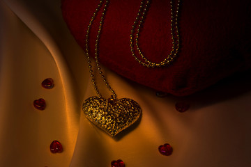 Love. Valentine's card. Gold heart on cord and red hearts on rustic fabric background.