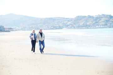 Senior couple walking on a sandy beach in winter