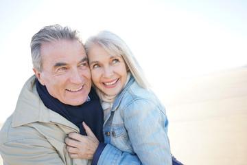 Portrait of senior couple having fun at the beach, wintertime