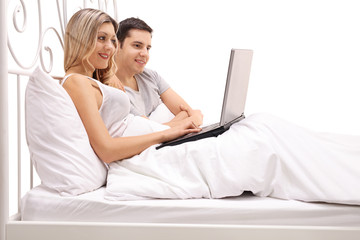 Happy young couple lying in bed and looking at a laptop