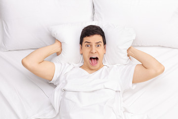 Man in bed screaming