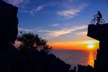 Men with bicycle on the top of the mountain and twilight sunset background.