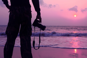 photographer with a camera and a purple sky sunrise on the beach.