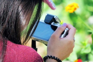 Young teenage girl taking photo and selfie with camera and nature background