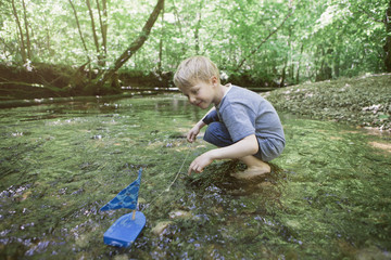 Boy playing with a toy boat in a forest brook