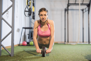 Young woman exercising with a wheel in gym