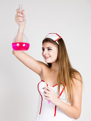 Beautiful smiling sexy nurse standing and holding test tube with pink liquid