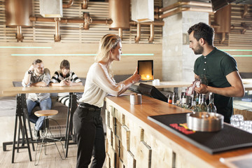Woman showing digital tablet to bartender