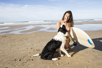 Happy woman with dog and surfboard on the beach