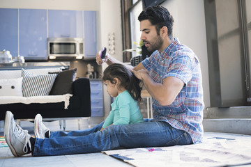 Father sitting on floor doing daughter's hair