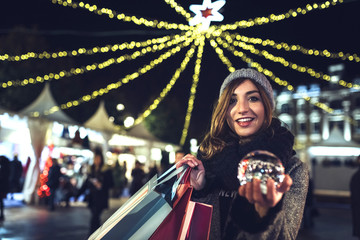 Portrait of happy woman holding bags and snow globe on the Christmas Market