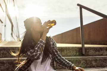 Young woman sitting on stairs drinking a beer from the bottle