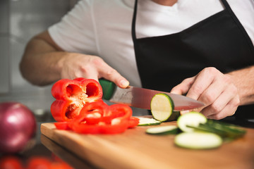 Chef hands cutting cucumber and pepper