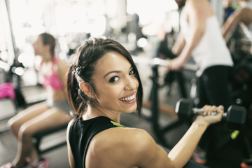 Portrait of smiling young woman lifting weights in gym