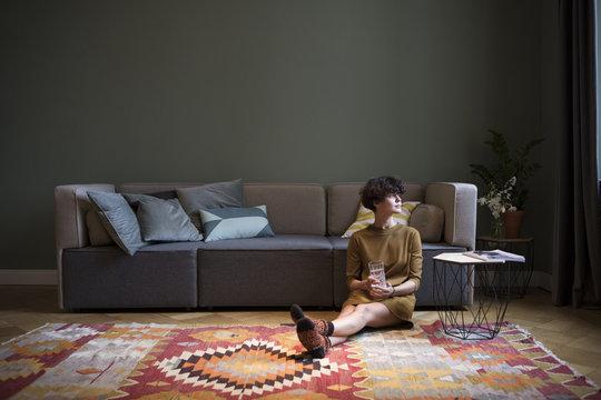 Woman sitting on floor in living room looking through window