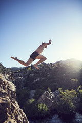 South Africa, Porterville, Beaverlac, man jumping from rock into water