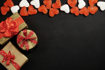Three gift boxes with red candies with copy space on black