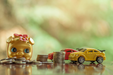 Gold piggy bank with coins and cars in concept saving money for car