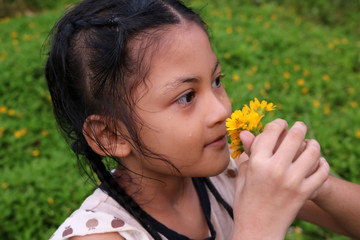 Thai cute girl with yellow flowers.