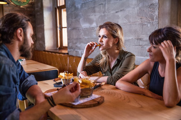 Group of friends eating snacks in coffee shop