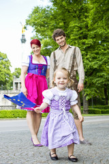 Girl waving European flag with parents in background