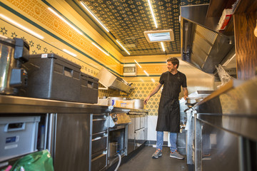 Entrepreneur with apron working in commercial kitchen at food truck