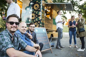 Group of customers relaxing next to food truck