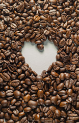 Coffebeans on Neutral Gray Background. Dark Roast Coffee. Heart.
