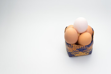 egg in basket on white background and single white egg