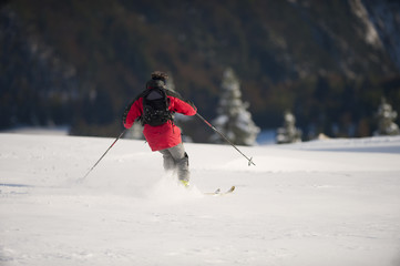 Man skiing downhill, view from his back