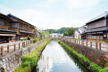 culture concept - japanese traditional historical wooden old house under morning blue cloudy sky and clear river