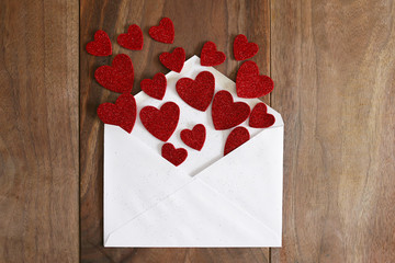 Valentine's Day Love Letter Spilling out Red Hearts onto Wood Ba
