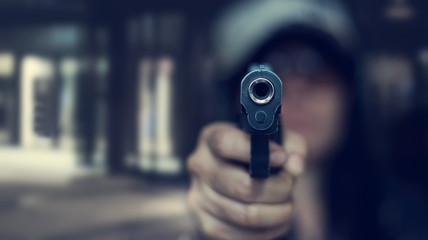 Woman pointing a gun at the target on dark background, selective focus