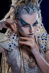 emotional actress woman in makeup and costume elf queen on blue-black background