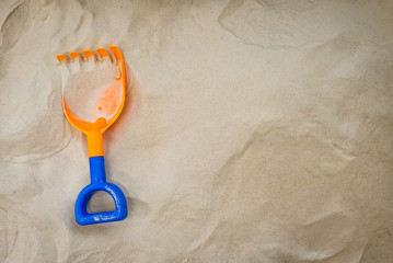 Toy Shovel on sandy background with copy space.