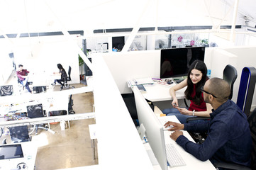 Young caucasian businesswoman with black male colleague in creative loft style workspace