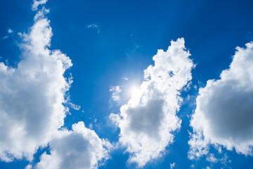 Looking up at sun behind cloud with nice blue sky
