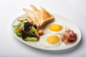 Fried eggs with toast and bacon.