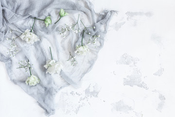 Composition with white flowers on gray background. Flat lay, top view