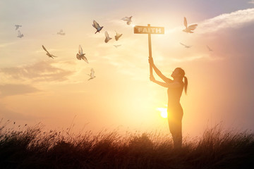 Fototapete - Woman holds a sign with word faith and flying birds on nature sunset