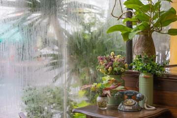 Flower vase on the table in rainy outside the mirror