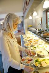 Senior woman in restaurant helping herself at delicatessen buffet