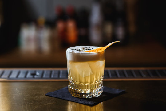 A light orange cocktail in an old fashioned glass, covered with egg-white foam. Decorated with sesame seeds and orange peel. Ice cubes inside. Selective focus.
