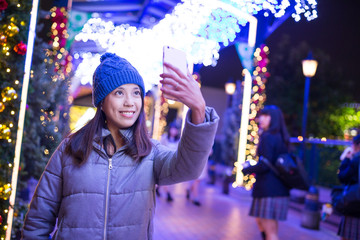 Woman taking selfie by mobile phone with christmas decoration at