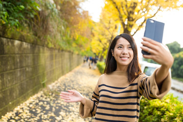 Woman using cellphone to take selfie with background of ginkgo t
