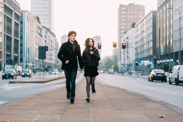 Young beautiful couple in love running outdoor in the city, having fun - first date,  romantic, love concept